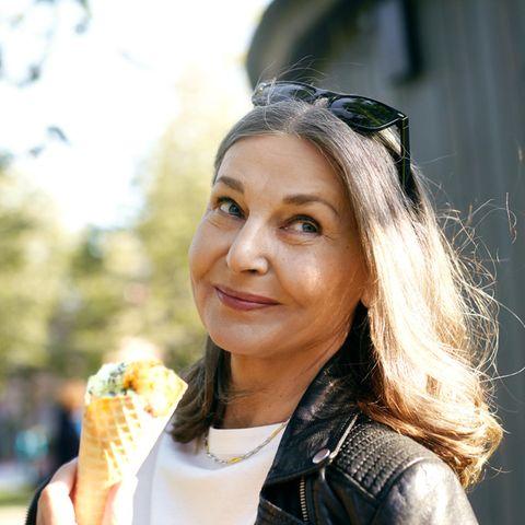 6 Lebensmittel, die Ihre Wechseljahre verschlimmern können: Frau mittleren Alters isst draußen ein Eis.