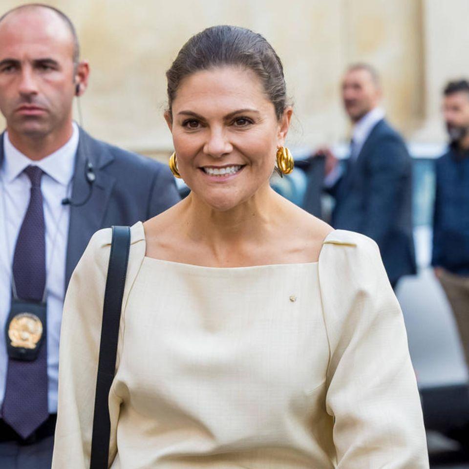Bei dem Besuch einer Bilderausstellung in Italien zeigt sich Prinzessin Victoria in einem eleganten Look aus cremefarbener Bluse und dunkelblauer Anzugshose mit goldenem Gürtel. Das schlicht anmutende Outfit besticht durch eineüberraschendeSchuhwahl: Die Ehefrau von Prinz Daniel trägt auffällige Ankle Boots in Schlangenleder-Optik des schwedischen Labels Stinaa.J, die dem Look eine trendige Note verleihen.