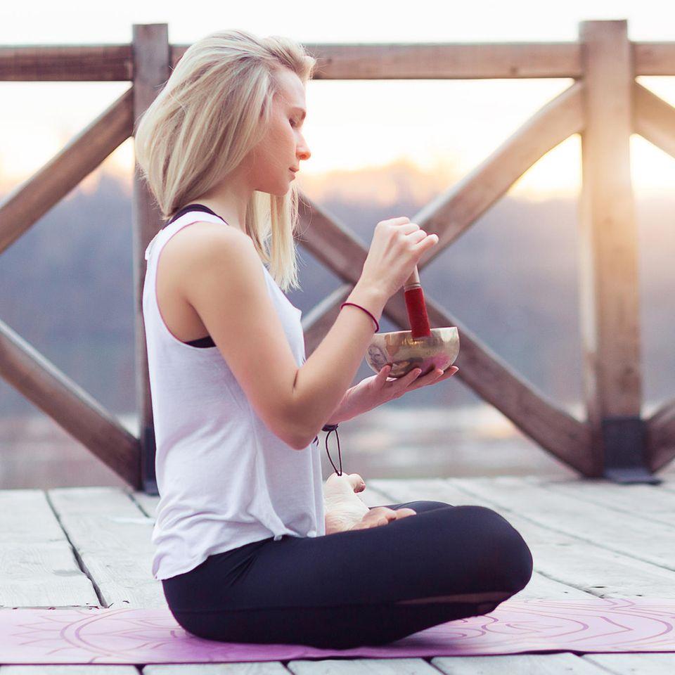 Das sind die 5 größten Yoga-Mythen – und wie es wirklich ist: Frau übt auf einem Steg Yoga mit Klangschale.