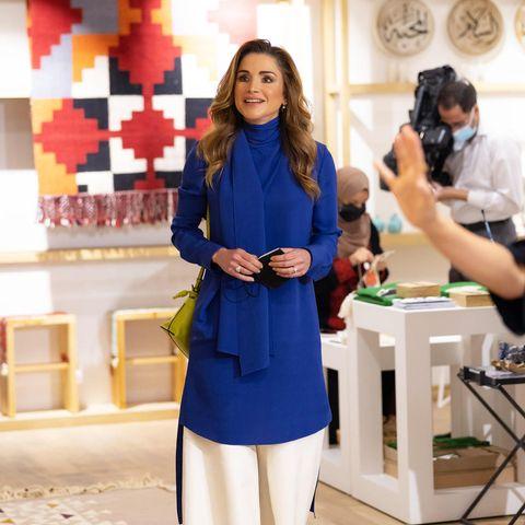Bei einem Besuch im Showroom von Jordan River Designs in Amman bezaubert Königin Rania in einer royalblauen Seidentunika und weißer Hose von Loewe und passenden Satin-High-Heels von Dior. Die limonengelbe Flamingo Clutch ebenfalls von Loewe, bildet zu diesem eleganten Look einen tollen farblichen Kontrast.