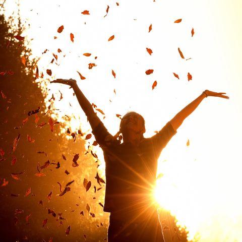 Horoskop: Lachende Frau wirft Blätter in die Luft