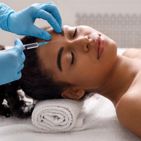 Ein Arzt injiziert einer Frau Botox zwischen den Augenbrauen