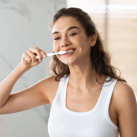 Frau putzt sich die Zähne vor dem Spiegel, Zahnpasta