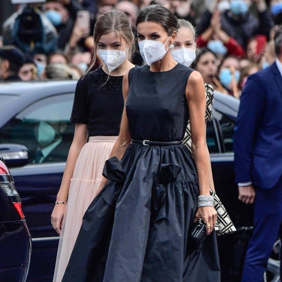 """Das""""Taffeta Bow Midi Dress"""" des spanischen Labels """"The 2nd Skin Co."""", das sie zur Verleihung desAsturien-Preises trägt, ist neu im Kleiderschrank der Königin. Der All-Black-Look verleiht Letizia Eleganz und Stärke gleichermaßen. Abgesehen vondem voluminösen Rockteil ist das Kleid eher schlicht gehalten. Die Frau von König Felipe weiß ihren Look aber aufzuwerten – und setzt dabei auf ein absolutes Trend-Piece!"""