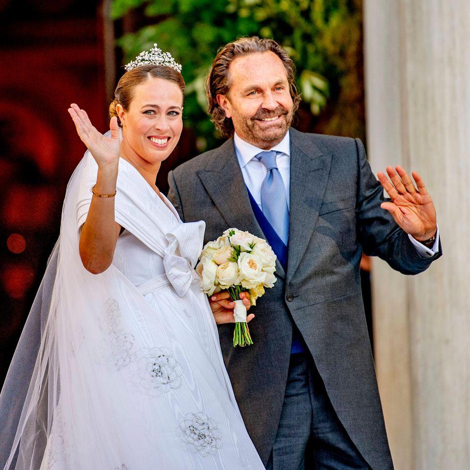 Am heutigen Samstag (23. Oktober 2021) gibt Nina Flohr ihrem Prinz Philippos von Griechenland und Dänemark das Jawort. Bei strahlendem Sonnenschein findetsich neben den Hochzeitsgästen vor derKathedrale Mariä Verkündigung in Athen auch die Braut ein und gewährt einen ersten Blick auf ihr pompöses Hochzeitskleid. Das Dress kommt mit opulentem Schleifen-Detail im Dekolleté-Bereich daher, die Schultern sind frei. Das Kleid ist in der Taille gebunden, geht dann über in einen weiten Rock aus fester Seide. Besonderes I-Tüpfelchen des Looks: am Rücken des Kleides brindet sich eine hoch sitzende Schleppe. Auch einen Schleier trägt die hübsche Braut, die sich hier an der Seite ihres Vaters Thomas zeigt. Der eher schlichte Schleier wird vollendet von einer Tiara, die ihr den royalen Touch verleiht.