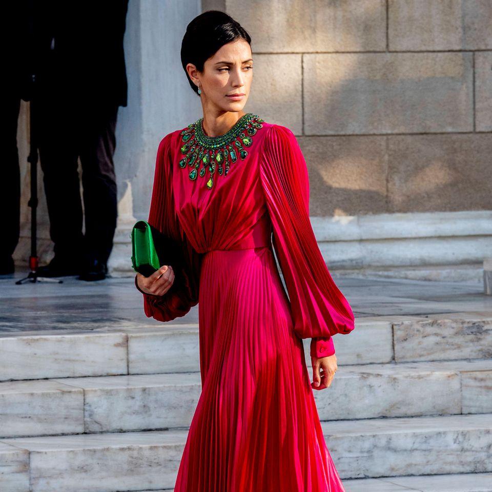 Eine der schönsten Frauen der Hochzeit: Alessandra de Osma wählt ein fließendes Kleid mit plissierten Ärmeln und Rockin einem kräftigen Beerenton und sieht darin einfach atemberaubend schön aus. Besonderer Eyecatcher: grüne Stein-Applikationen im Dekolleté sowie die darauf farblich abgestimmte Clutch. Besser geht es nicht.