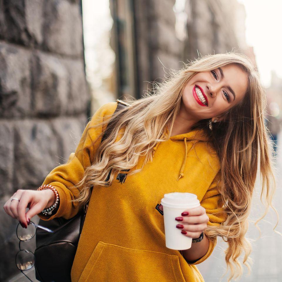 Eine Frau in einer herbstlichen Fußgängerzone lacht fröhlich in die Kamera.