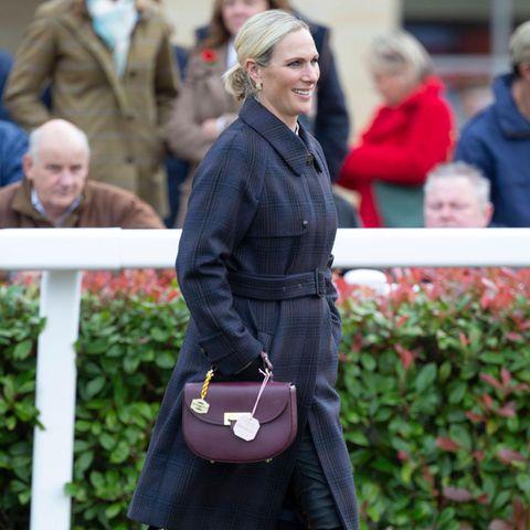 Zara Tindall besucht das Showcase Meeting am Cheltenham Racecours. Für den aufregenden Tag setzt die Britin auf einen Karomantel von Really Wild und enganliegende kniehohe Stiefel von Fairfax & Favor. Ein weiteres Highlight: ihre Ledertasche in herbstlichem Bordeaux von Aspinal of London.