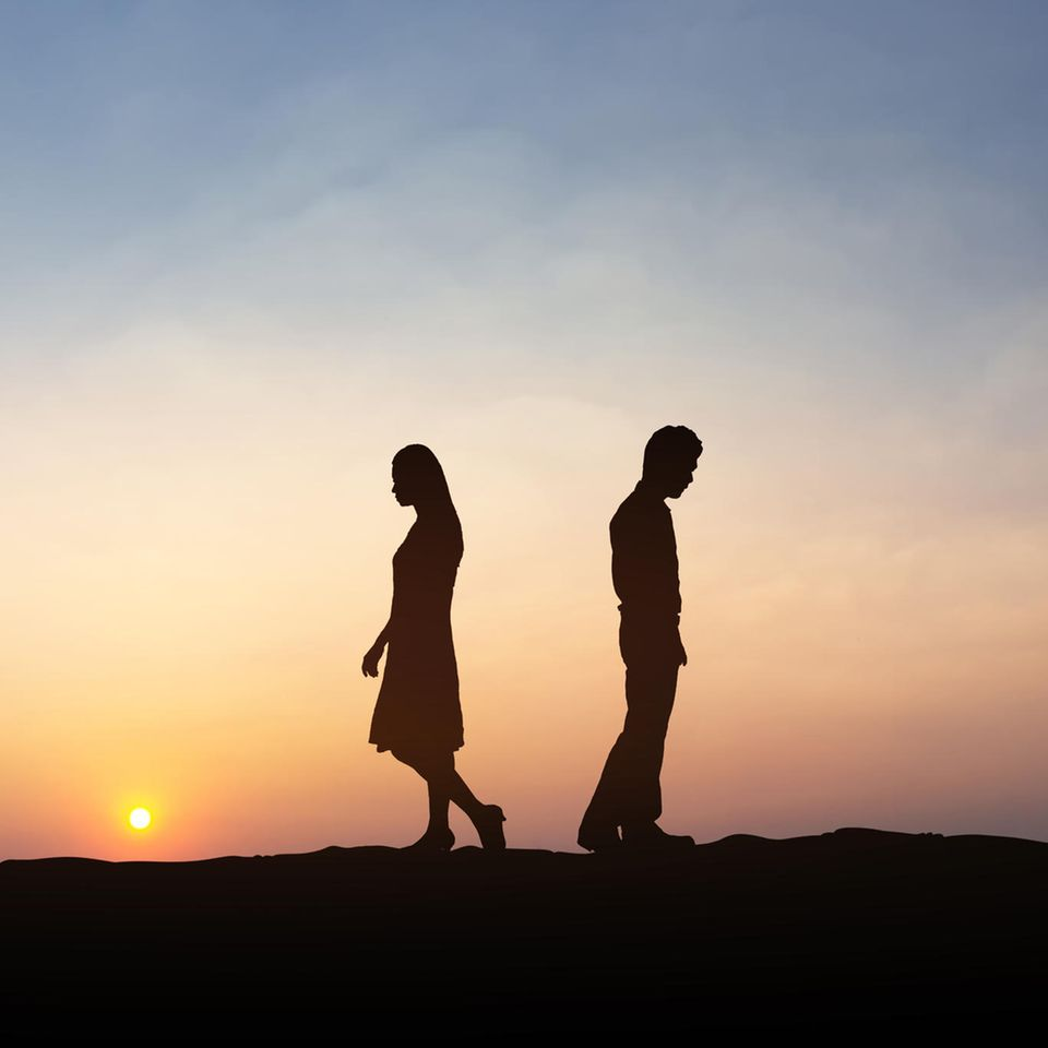 Ein Paar geht auseinander während die Sonne untergeht.