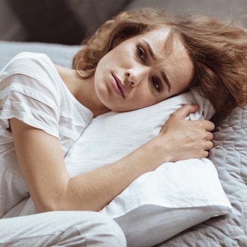 Selbstmitgefühl: Frau liegt traurig auf dem Sofa