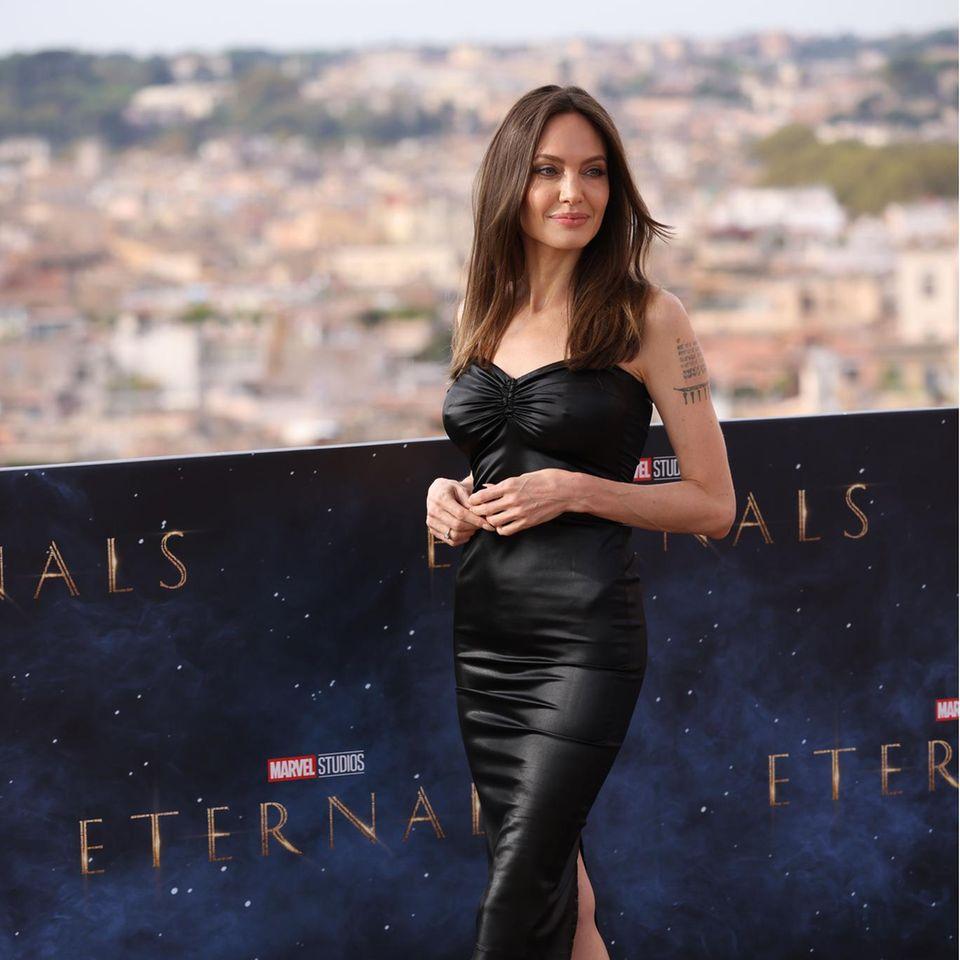 """Auf dem roten Teppich des Films """"Eternals"""" beweist Schauspielerin Angelina Jolie, dass sie nicht nur in Glitzer und Glamour gut aussieht, sondern auch im sexy Lederkleid eine hammermäßige Figur macht. Das trägerlose Midikleid mit Raffungen ist unaufgeregt und cool – genauso wie sie. Und zum Glück: Ihre Extentions hat sie diesmal zuhause gelassen ..."""