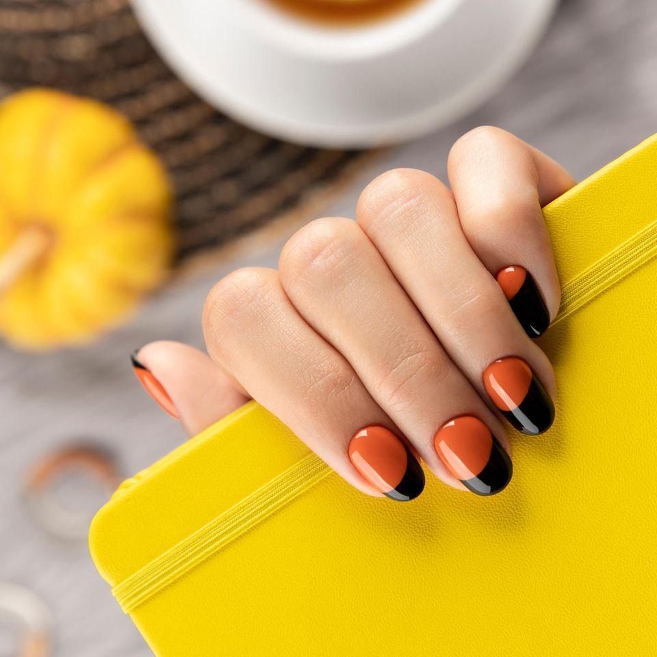 Halloween-Nägel 2021: Eine Hand mit orange-schwarz lackierten Nägeln