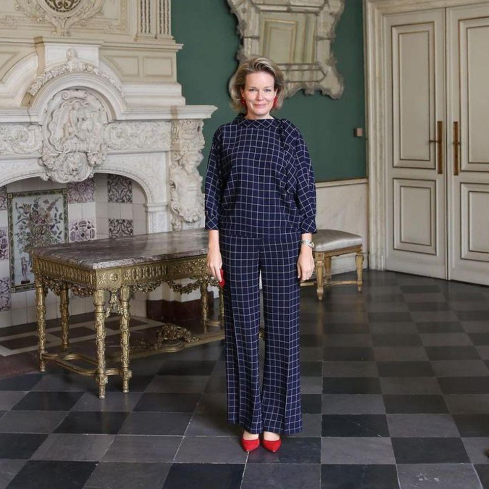 Königin Mathilde zeigt sich im eleganten Zweiteiler von Carolina Herrera. Bei ihrem Treffen mit den Generaldirektoren von De Gzinsbond und la Ligue des Familles vervollständigt die belgische Königin ihren Look mit auffällig roten Pumps und passenden Ohrringen. Ein stilvoll eleganter Auftritt.